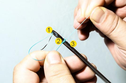 Собранные витки в едином узле на корпусе иглодержателя в промежутке между браншами и фиксатором узла.